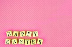 Happy Easter wooden blocks over pink Stock Photo