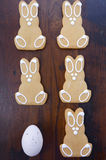 Happy Easter Wooden Bunnies. Happy Easter gingerbread cookie bunnies on a dark wood table background royalty free stock photography