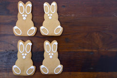 Happy Easter Wooden Bunnies. Happy Easter gingerbread cookie bunnies on a dark wood table background, with copy space royalty free stock photos