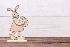 Happy easter! Wooden bunny on a wooden background. Easter conceptual background Royalty Free Stock Photography