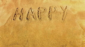 Happy Easter. Words Happy Easter appearing letter by letter on the golden sandy beach. Letters are handwritten