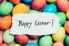 `Happy Easter` written on a piece of white paper. Colorful eggs. Holiday wishes Stock Image