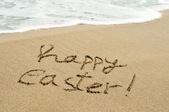 Happy easter written in the sand of a beach Royalty Free Stock Image