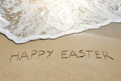 Happy easter written on sand Stock Photos