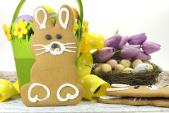 Happy Easter yellow and lime green theme gingerbread bunny cookie with basket, tulips, and candy birds eggs royalty free stock photography