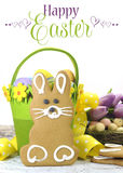 Happy Easter yellow and lime green theme gingerbread bunny cookie with basket, tulips, and candy birds eggs with ssample text Stock Photo
