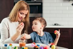 Happy Easter Young mother and her little son painting Easter eggs. royalty free stock photography
