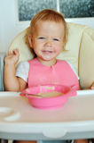Happy eating baby girl Stock Photography