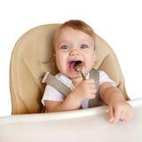 Happy eating baby in a high chair. Stock Photos