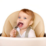 Happy eating baby in a high chair. Royalty Free Stock Photo