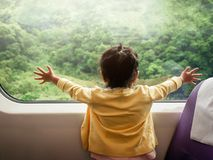 Happy and Ecxited Kids Traveling by Train. A Two Years old Girl. Looking through Wide Glass Window. Green Forest as Outside View Stock Photography