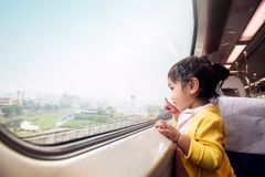 Happy and Ecxited Kids Traveling by Train. A Two Years old Girl. Pointing her hand to Outside View, Sitting Near Wide Glass Window and Smiling stock image