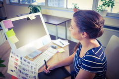 Happy editor working at her desk. In creative office stock photos