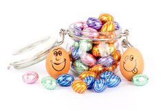 Happy eggs between chocolate easter eggs Royalty Free Stock Images