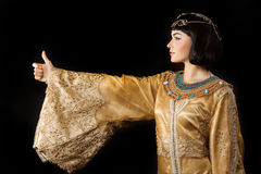 Happy Egyptian woman like Cleopatra with thumbs up gesture, on black background. Thumbs up. Glamorous closeup portrait of beautiful stylish brunette young woman royalty free stock image