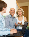 Happy eldelry couple talking with employee with laptop Royalty Free Stock Photos