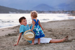 Happy elder brother is playing with his younger sister. Happy elder brother is playing with his younger pretty sister on sand near sea Royalty Free Stock Image