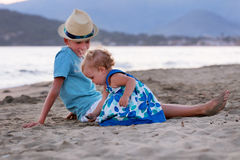 Happy elder brother is playing with his younger sister. Happy elder brother is playing with his younger pretty sister on sand near sea Royalty Free Stock Photography