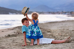 Happy elder brother is playing with his younger sister. Happy elder brother is playing with his younger pretty sister on sand near sea Stock Photo