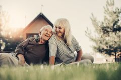 Happy elder couple in front of blurred house Stock Photo