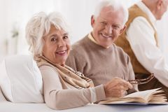 Happy elder is looking at wife. Which is reading book in bright room Stock Photos
