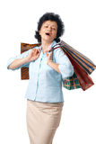 Happy Elder Shopper. Happy elderly woman with shopping bags over white background Stock Image