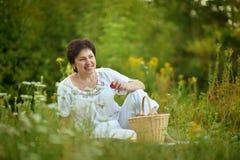 Happy elder woman resting on grass Stock Photo