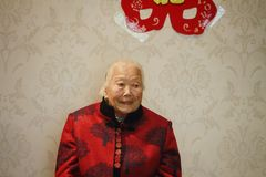 Happy elderly Asian Chinese 90s old woman portrait on her grandson wedding. Happy Asian Chinese old woman, 93 years old, up to 90s , silvery hair, golden earing Stock Photos