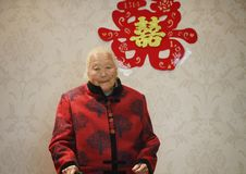 Happy elderly Asian Chinese 90s old woman portrait on her grandson wedding. Happy Asian Chinese old woman, 93 years old, up to 90s , silvery hair, golden earing Royalty Free Stock Photography