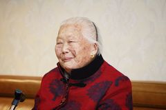 Happy Elderly Asian Chinese 90s old woman portrait laugh. Happy Asian Chinese old woman, 93 years old, up to 90s , silvery hair, golden earing on her ear Royalty Free Stock Images