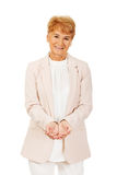 Happy elderly business woman holding copyspace or something on open palms.  Royalty Free Stock Images