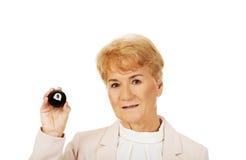 Happy elderly business woman holding eight billard-ball.  Royalty Free Stock Photos