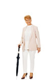 Happy elderly business woman holding an umbrella Stock Photo