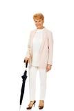 Happy elderly business woman holding an umbrella Stock Photo