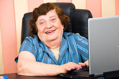 Happy elderly business woman using laptop. Close up of beautiful laughing elderly business woman working on laptop in an office,check also royalty free stock photography