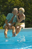 Happy Elderly couple. Having fun while sitting on the poolside and teasing each other Royalty Free Stock Photos