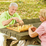 Happy elderly couple. Has fun playing chess in the park Stock Photos