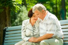 Happy elderly couple. Listening music in headset or praying together, outdoors Royalty Free Stock Image