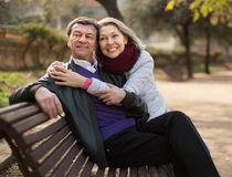 Happy elderly couple on a bench in the park in autumn day Royalty Free Stock Photography