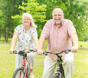Happy elderly couple. With bike in the park Stock Photography