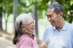 Happy elderly couple chatting in the park. Close up of elderly couple looks happy while chatting together in the park royalty free stock image