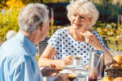 Happy elderly couple eating breakfast in their garden outdoors i Stock Photos