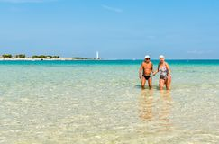 Happy elderly couple enjoys a romantic walk in the crystal clear water on the San Vito Lo Capo beach. Stock Photos
