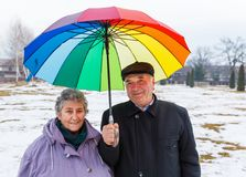 Happy elderly couple. Under colorful umbrella walking in the park Royalty Free Stock Photos
