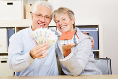 Happy elderly couple with house Stock Images