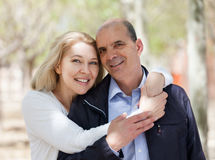 Happy elderly couple hugging in park and smiling Royalty Free Stock Photography