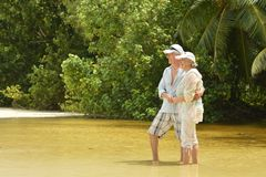 Elderly couple  hugging  on  tropical beach. Happy elderly couple  hugging  on  tropical beach Royalty Free Stock Photography