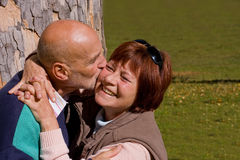 Happy elderly couple kissing. Husband kissing his wife on cheek Stock Images