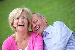 Happy elderly couple laughing together. Happy attractive elderly couple laughing together as they snuggle affectionately while relaxing outdoors on the grass Royalty Free Stock Photography