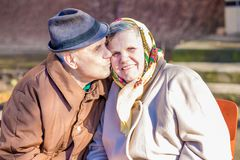 Happy elderly couple in love celebrating their anniversary. A happy and loving elderly man kisses his beloved wife on the cheek. Happy elderly couple in love Stock Image